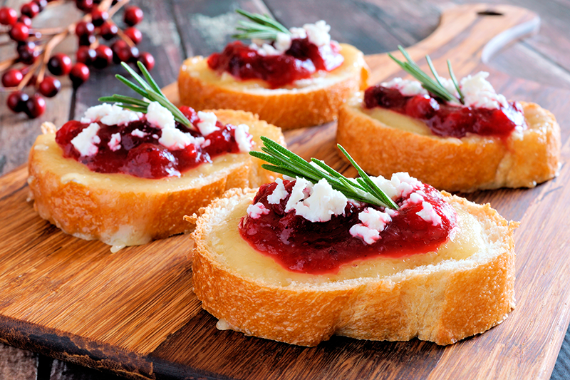 Holiday-crostini-appetizers-with-cranberry-sauce,-brie,-feta-and-rosemary-on-a-wooden-server